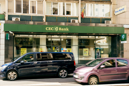 BUCHAREST, ROMANIA - APR 1, 2016: Cars driving fast on Bucharest boulevard with CEC bank agency in the background. CEC Bank is a state-owned Romanian banking institution Редакционное