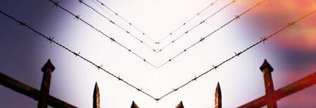 Escape concept - prison fence in barbed wire fence closeup - security anti-escape concept Stock Photo