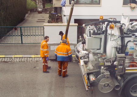 metal grate: PARIS, FRANCE - DEB 10, 2017: Workers using sewerage truck and large pipe working on the clogged street rain water drain repairing and maintenance