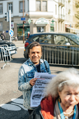STRASBOURG, FRANCE - APR 8, 2017: Political agitation at French market for the upcoming French presidential election 2017 -  Parti ouvrier independant newspaper distribution by man