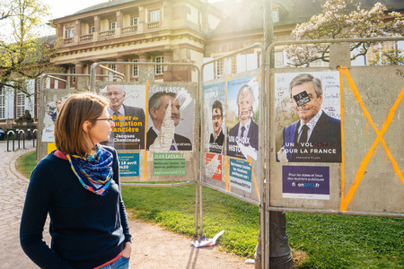 emmanuel: STRASBOURG, FRANCE - APR 12, 2017: Woman looking at official campaign posters of Francois Fillon and other political party leaders of eleven candidates running in the 2017 French presidential election