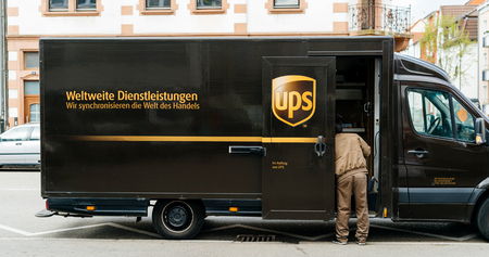 KEHL, GERMANY - APR 6, 2017: UPS United Parcel Service van delivery brown UPS van parked on a street with driver worker searching for the parcel in the van interior
