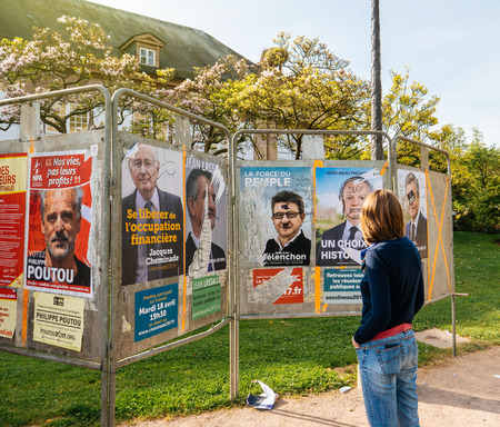 emmanuel: STRASBOURG, FRANCE - APR 12, 2017: Woman looking at official campaign posters of Jean-Luc Melenchon and other political party leaders of eleven candidates running in the 2017 French presidential election