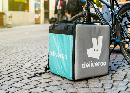 STRASBOURG, FRANCE - APR 3, 2017: Detail of Deliveroo bike and cargo box parked in city with cafe terrace restaurant in the bakground to deliver on time the food to the client. Deliveroo is a British online food delivery company with operations spread acr