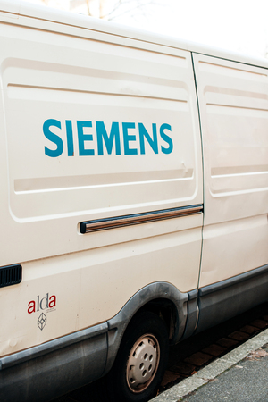 ag: STRASBOURG, FRANCE - FEB 13, 2017: Rear view of white van from Siemens corporation parked on a street. Siemens AG is a German conglomerate company headquartered in Berlin and Munich and the largest manufacturing and electronics company in Europe with bran