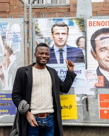emmanuel: STRASBOURG, FRANCE - APR 23, 2017: Black ethnicity man showing his support to Emmanuel Macron near all 11 presidential posters