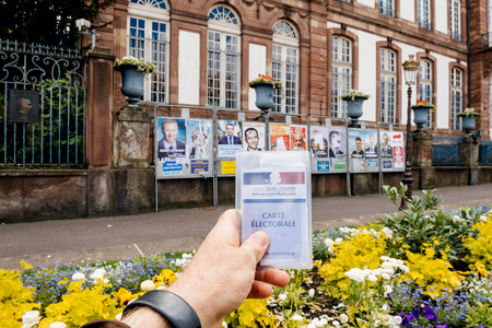 agitation: STRASBOURG, FRANCE - APR 23, 2017: Man holding Carte Electorale - voters card French voter registration card in front of official campaign posters for all eleven candidates for the 2017 French presidential elections outside pooling station Editorial