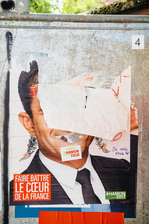 STRASBOURG, FRANCE - APR 23, 2017: Official campaign posters of Benoit Hamon,political party leader of Parti socialiste (PS), vandalized on the first round of 2017 French presidential election Editorial