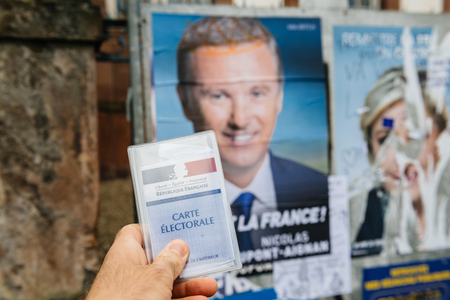 STRASBOURG, FRANCE - APR 23, 2017: French voter registration card held by male hand in front of official campaign poster of Nicolas Dupont-Aigna  candidate for the 2017 French presidential elections posted outside a polling station