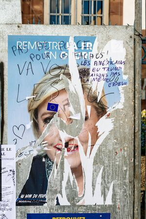 agitation: STRASBOURG, FRANCE - APR 23, 2017: Official campaign posters of Marine Le Pen, political party leader of Front national (FN) vandalized on the first round of 2017 French presidential election Editorial