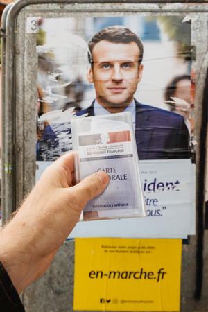 emmanuel: STRASBOURG, FRANCE - APR 23, 2017: French voter registration card held by male hand in front of official campaign poster of Emmanuel Macron  candidate for the 2017 French presidential elections posted outside a polling station