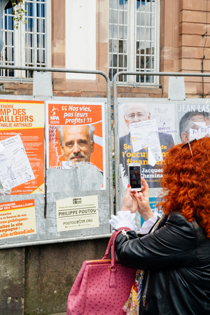 fro: STRASBOURG, FRANCE - APR 23, 2017: Woman taking on mobile phone Presidential campaign posters of candidates fro French presidency Editorial