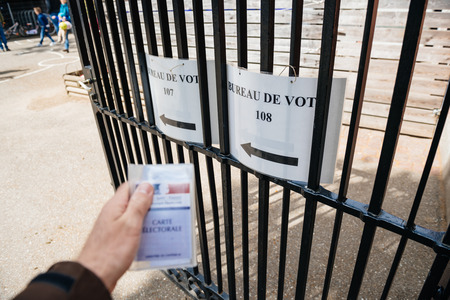 STRASBOURG, FRANCE - APR 23, 2017: French voter registration card held by male hand in front of Bureau de Vote  Voting Section open for the 2017 French presidential elections posted outside a polling station
