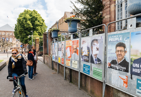agitation: STRASBOURG, FRANCE - APR 23, 2017: People looking at the official campaign posters for all eleven candidates for the 2017 French presidential elections posted outside a polling station