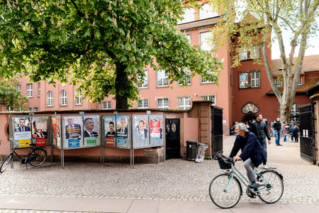 agitation: STRASBOURG, FRANCE - APR 23, 2017: Cyclist in front of French presidential campaign posters during first election day in France Editorial