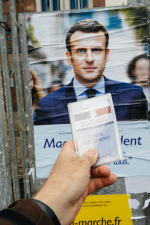 STRASBOURG, FRANCE - APR 23, 2017: French voter registration card held by male hand in front of official campaign poster of Emmanuel Macron  candidate for the 2017 French presidential elections posted outside a polling station