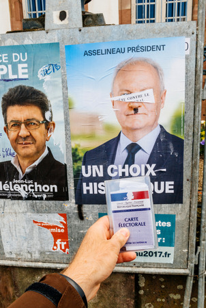agitation: STRASBOURG, FRANCE - APR 23, 2017: French voter registration card held by male hand in front of official campaign poster of Francois Asselineau  candidate for the 2017 French presidential elections posted outside a polling station Editorial