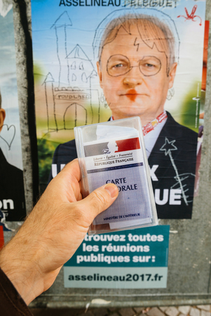 STRASBOURG, FRANCE - APR 23, 2017: French voter registration card held by male hand in front of official campaign poster of Francois Asselineau  candidate for the 2017 French presidential elections posted outside a polling station Editorial