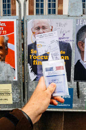 agitation: STRASBOURG, FRANCE - APR 23, 2017: French voter registration card held by male hand in front of official campaign poster of Jacques Cheminade  candidate for the 2017 French presidential elections posted outside a polling station