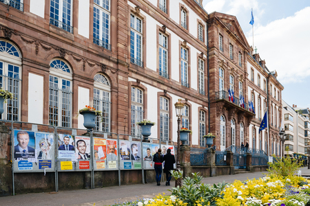 STRASBOURG, FRANCE - APR 23, 2017: Black ethnicity man and caucasian woman admiring official campaign posters for all eleven candidates for the 2017 French presidential elections posted outside a polling station at City Hall pooling station