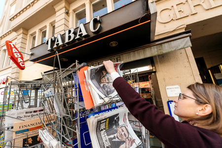 emmanuel: PARIS, FRANCE - APRIL 24: Woman buy looks at press kiosk at French newspaper Liberation, Aujordhui,  with pictures of French Presidential election candidates, Emmanuel Macron, Marine Le Pen a day after first round of French Presidential election on April