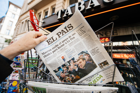 PARIS, FRANCE - APRIL 24: Man buy looks at press kiosk at Spanish El Pais newspaper with pictures of French Presidential election candidates, Emmanuel Macron, Marine Le Pen a day after first round of French Presidential election on April 23, 2017