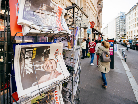 emmanuel: PARIS, FRANCE - APRIL 24: Woman buy looks at press kiosk at French newspaper with pictures of French Presidential election candidates, Emmanuel Macron, Marine Le Pen a day after first round of French Presidential election on April 23, 2017