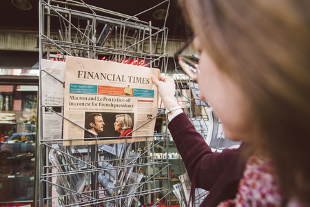 emmanuel: PARIS, FRANCE - APRIL 24: Woman buy looks at press kiosk at UK newspaper  with pictures of French Presidential election candidates, Emmanuel Macron, Marine Le Pen a day after first round of French Presidential election on April 23, 2017 Editorial