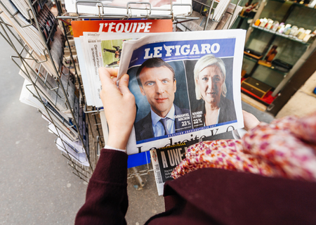 emmanuel: PARIS, FRANCE - APRIL 24: Woman looks at press kiosk at French newspaper Le Figaro with pictures of French Presidential election candidates, Emmanuel Macron, Marine Le Pen a day after first round of French Presidential election on April 23, 2017 Editorial