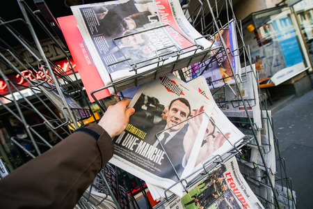 emmanuel: PARIS, FRANCE - APRIL 24: Man buy looks at press kiosk at French newspaper Liberation  with pictures of French Presidential election candidates, Emmanuel Macron a day after first round of French Presidential election on April 23, 2017