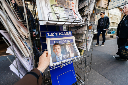 emmanuel: PARIS, FRANCE - APRIL 24: Man buy looks at press kiosk at French newspaper  with pictures of French Presidential election candidates, Emmanuel Macron, Marine Le Pen a day after first round of French Presidential election on April 23, 2017