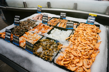 shop for animals: Supermarket stall with langoustine, bulot cuit, noix saint jacques, crevettes, calamar, rouget barbet - fresh fish counter full with diverse - organic fish meat Stock Photo