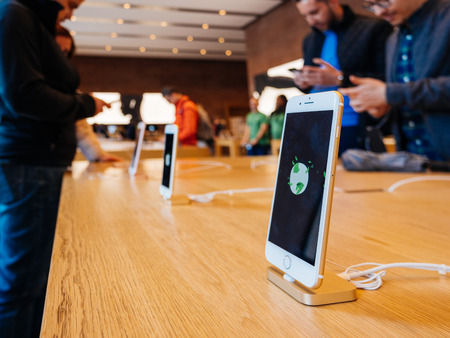 retina display: STRASBOURG, FRANCE - APR 27, 2016: Latest iPhone 7 and iPhone 7 Plus in Apple Store with screensaver dedicated to Earth Day  - customers shopping testing in the background Editorial