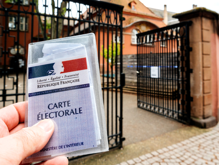 STRASBOURG, 프랑스 -2011 년 5 월 7 일 : 지주 카드 Electorale- 유권자의 카드를 들고하는 남자 Emmanuel Macron와 마린 르 펜 중 선택하는 프랑스 대통령 선거의 두
