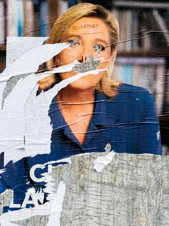 STRASBOURG, FRANCE - MAY 7, 2017: Le Pen damaged poster during the second round of the French presidential election to choose between Emmanuel Macron and Marine Le Pen