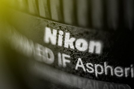 headquartered: FRANKFURT, GERMANY - SEPT 19, 2011: Focusing technique effect over the Nikon Lens. Nikon is a Japanese multinational corporation headquartered in Tokyo, Japan, specializing in optics and imaging products.