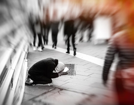 unneeded: People passing indifferently next to beggar in the street of the modern city - black and white image vintage filter applied red flare