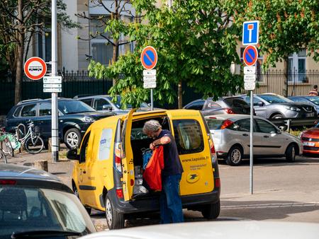 STRASBURGO, FRANCIA - 12 APRILE 2017: Furgone giallo di La Poste - servizio postale nazionale francese con l'operaio del driver postale che cerca gor il pacchetto giusto per consegnare vicino a costruzione francese