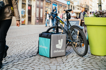 STRASBOURG, FRANCE - APR 3, 2017: Deliveroo cargo box near a parked bicycle with cafe terrace restaurant in the background to deliver on time the food to the client. Deliveroo is a British online food delivery company with operations spread across eighty- Editorial