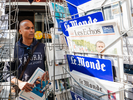 french ethnicity: PARIS, FRANCE - MAY 15, 2017: Black ethnicity man buying Le monde newspaper reporting handover ceremony presidential inauguration of the newly elected French President Emmanuel Macron in Paris, France