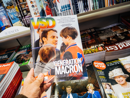 tributos: PARIS, FRANCE - MAY 15, 2017: Man buys VSD magazine with Macron Generation on cover French President Emmanuel Macron in Paris, France