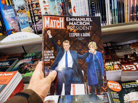 handover: PARIS, FRANCE - MAY 15, 2017: Man buys Paris Match magazine with Emmanuel Macron and his wife Brigitte Trogneux during handover ceremony presidential inauguration of the newly elected French President Emmanuel Macron in Paris, France