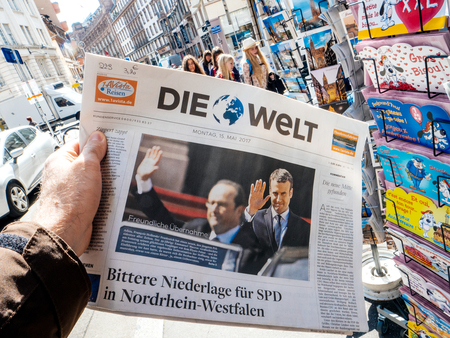 tributos: PARIS, FRANCE - MAY 15, 2017: Man buys German Die Welt newspaper reporting handover ceremony presidential inauguration of the newly elected French President Emmanuel Macron in Paris, France