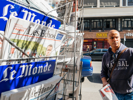 tributos: PARIS, FRANCE - MAY 15, 2017: Black ethnicity man buying Le monde newspaper reporting handover ceremony presidential inauguration of the newly elected French President Emmanuel Macron in Paris, France