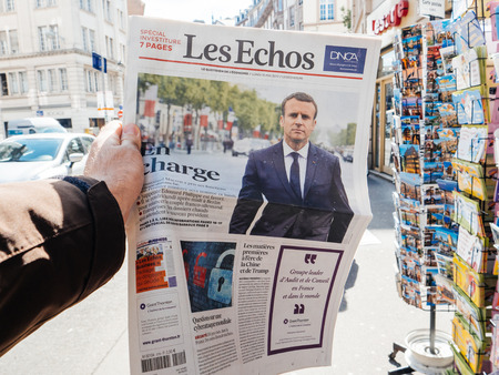 tributos: PARIS, FRANCE - MAY 15, 2017: Man buys Les Echo newspaper reporting handover ceremony presidential inauguration of the newly elected French President Emmanuel Macron in Paris, France