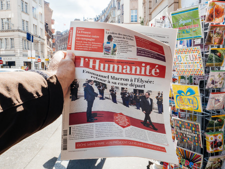 handover: PARIS, FRANCE - MAY 15, 2017: Man buys LHumanite, French newspaper reporting handover ceremony presidential inauguration of the newly elected French President Emmanuel Macron in Paris, France Editorial