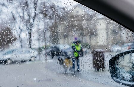 Silhouette of postman postal worker on bike crossing street on a snowy day - senn by the driver point ov view personal perspective through wet windshield window Stock Photo