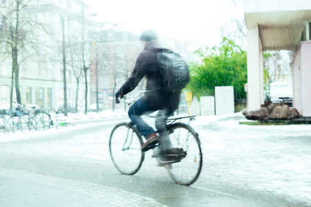 sihlouette: Sihlouette of adult cyclist motion on snow on a snowy winter day