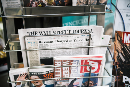 PARIS, FRANCE - MAR 23, 2017: The Wall Street Journal and other international magazines covers at press kiosk newsstand featuring headlines about the Russians Charged for the Yahoo hack Sajtókép