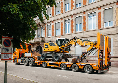 compact track loader: STRASBOURG, FRANCE - MAY 18, 2016: Liebherr 912 compact excavator on transportation trailer in urban environment with luxury apartment office historic building behind Editorial